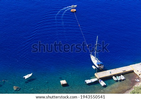 View from above, aerial picture of a wooden pier with small boats and a sail boat anchored in the transparent turquoise sea in Santorini, Greece.