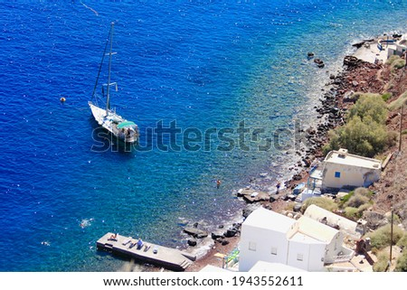 View from above, aerial picture of a sail boat with tourists, anchored in the transparent turquoise sea in Santorini, Greece. Waterfront beach houses and tourists sun bathing on a pier in foreground.