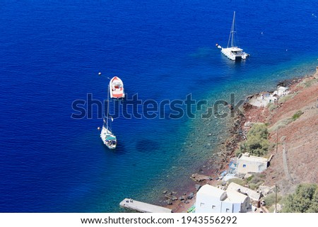 View from above, aerial picture of a sail boat, inflatable boat and catamaran, all anchored in the transparent turquoise sea in Santorini, Greece. Waterfront beach houses in foreground.