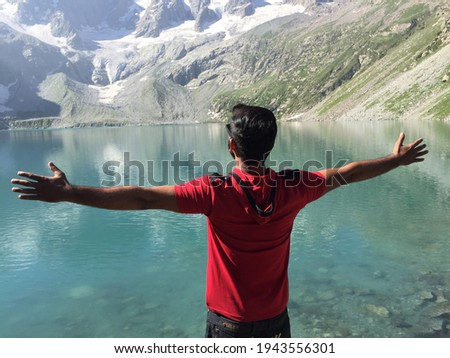 Unrecognizable man wearing a red shirt standing with open hands facing towards the Kumrat lake with snow placed on mountains and mountains reflection in Kumrat lake at Kumrat valley, Pakistan. Royalty-Free Stock Photo #1943556301