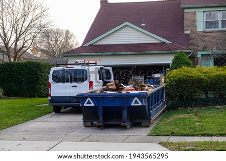 Low blue dumpster full of cardboard and construction debris in front of a full garage and next to a white worker's van Royalty-Free Stock Photo #1943565295