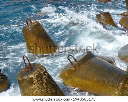 Marine concrete breakwaters (anchors) in shallow water. Traveling-wave protection, concrete breakwater Royalty-Free Stock Photo #1943585173