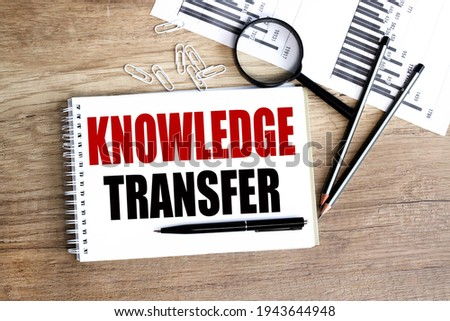 knowledge transfer. text on white paper on wood background