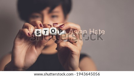 """Stop asian hate hashtag, support Asian americans communities, stop hate crimes campaign. A beautiful Asian woman hold letter word """"STOP"""". Hate is a virus, Against racism, Campaign, Anti-AAPI, Concept. Royalty-Free Stock Photo #1943645056"""