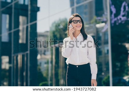Photo portrait of business woman wearing white shirt black pants spectacles talking on mobile phone smiling on work pause
