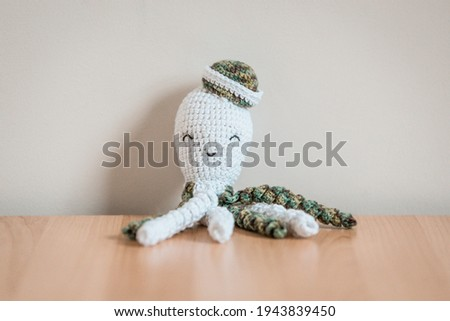 A squid or octopus soft plush toy for a child or infant, made from crochet yarn. Pictured on a light wooden surface