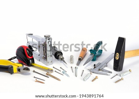 Tools and parts are on a white background. Metal object. A group of repair tools. Various parts and spare parts on the table. Tools for men. A set of working tools. Royalty-Free Stock Photo #1943891764