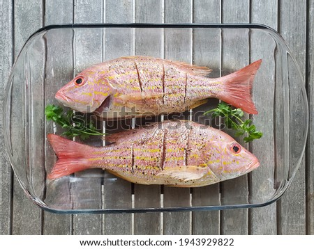 Two fresh, whole lane snapper prepared for cooking. Royalty-Free Stock Photo #1943929822