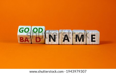 Good or bad name symbol. Turned wooden cubes and changed words 'bad name' to 'good name'. Beautiful orange background, copy space. Business and good or bad name concept. Royalty-Free Stock Photo #1943979307