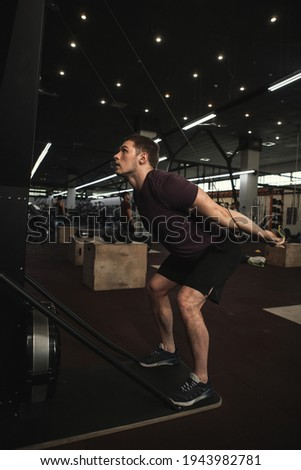 Vertical shot of a male athlete working out on ski erg machine at the gym Royalty-Free Stock Photo #1943982781
