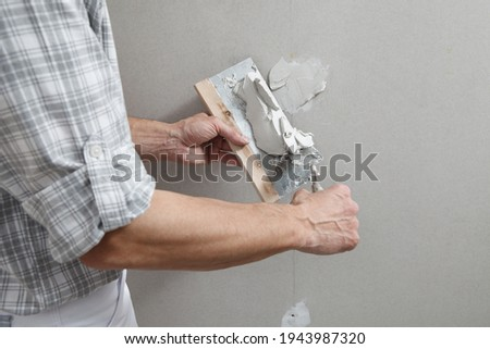 closeup hands man drywall worker or plasterer putting stucco on plasterboard wall using a trowel and a spatula, fill the screw holes Royalty-Free Stock Photo #1943987320