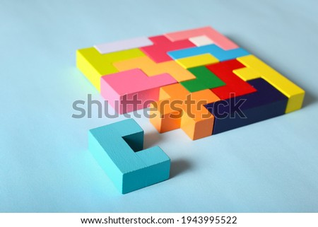 Concept of creative, logical thinking. Different colorful shapes wooden blocks on light background. Geometric shapes in different colors. Child development. Riddle and its solution. Logic tasks. Royalty-Free Stock Photo #1943995522