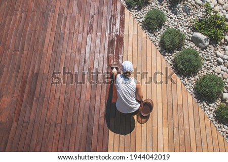 Wood deck renovation treatment, the person applying protective wood stain with a brush, overhead view of ipe hardwood decking restoration process Royalty-Free Stock Photo #1944042019