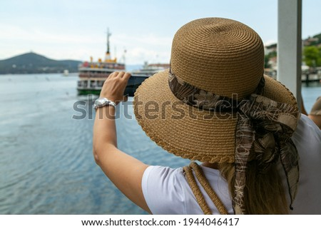 Young travelling woman in straw hat doing shots of sailing ship in summer day. Tourist girl on excursions with phone camera taking pictures. Vacation relax time. Travel concept with copy space area.