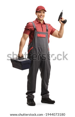 Full length portrait of a repairman with a tool box and a drill isolated on white background Royalty-Free Stock Photo #1944073180