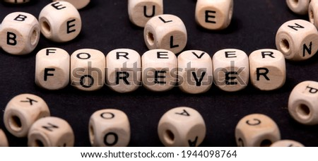 The word FOREVER on wooden cubes around cubes with letters