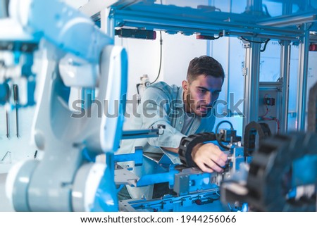 Meeting asian Engineers Maintenance Robot Arm at Lab. they are in a High Tech Research Laboratory with Modern Equipment.Professional Japanese Development Engineer is Testing an Artificial Intelligent. Royalty-Free Stock Photo #1944256066