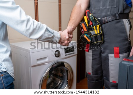 Close-up of a repairman shaking hands with a female customer. Male repairman for washing machine repair Royalty-Free Stock Photo #1944314182