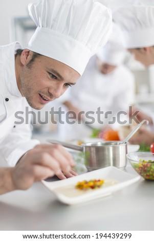 closeup on chef garnishing a plate #194439299