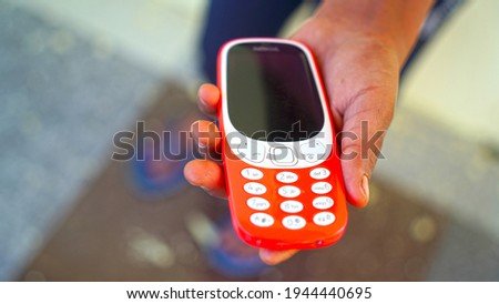Selective focus on the keypad of a mobile. Beautiful red phone in Human hand. Keypad phone concept. Royalty-Free Stock Photo #1944440695