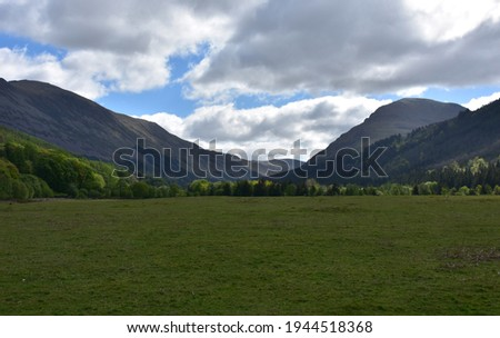 Large field in a valley between two mountain ranges. Royalty-Free Stock Photo #1944518368