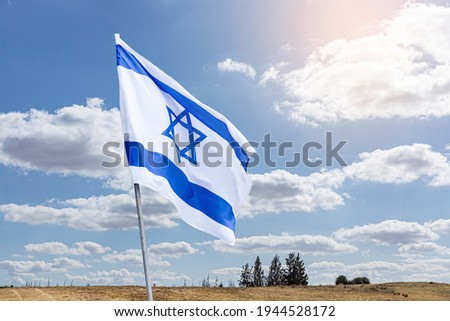 The flag of Israel on a field and a cloudy sky background. Memorial day-Yom Hazikaron, Patriotic holiday Independence day Israel - Yom Ha'atzmaut concept. Royalty-Free Stock Photo #1944528172