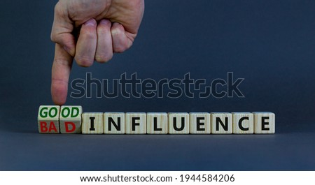 Good or bad influence symbol. Businessman turns cubes and changes words 'bad influence' to 'good influence'. Beautiful grey background. Business, good or bad influence concept. Copy space. Royalty-Free Stock Photo #1944584206