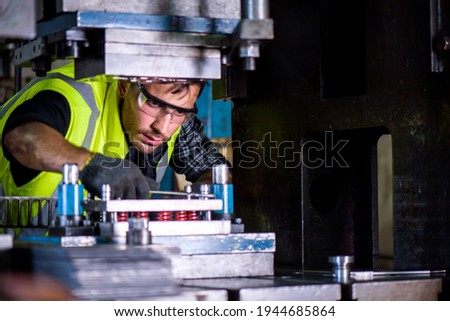 Caucasian engineer mechanic man checking for maintenance pressing metal machine at factory, worker at industrial working concept Royalty-Free Stock Photo #1944685864