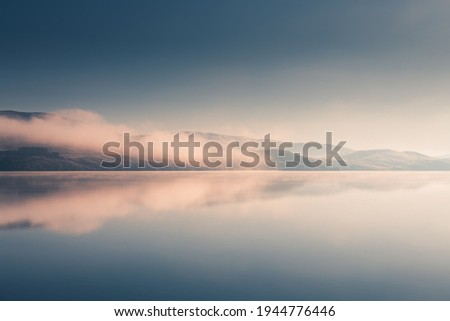 Beautiful lake in misty morning. Mountains and clouds are reflected in the calm water surface. Autumn landscape. South Ural, Russia. Royalty-Free Stock Photo #1944776446