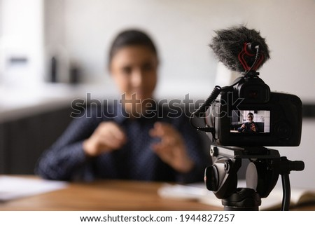 Close up Indian blogger using professional digital camera, recording video, tutorial or vlog, sitting at work desk, young woman teacher business coach shooting webinar, speaking, explaining,