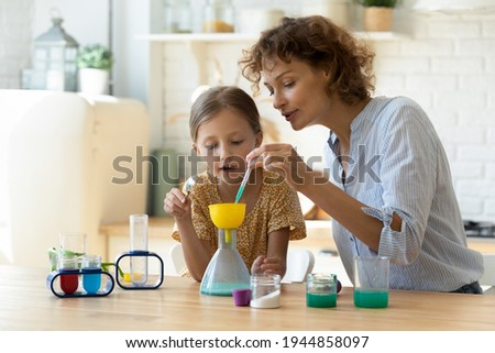 Excited young Caucasian mother and little 9s daughter have fun play with chemistry lab game together. Caring playful mom and small teen girl child engaged in interesting scientific activity at home. Royalty-Free Stock Photo #1944858097