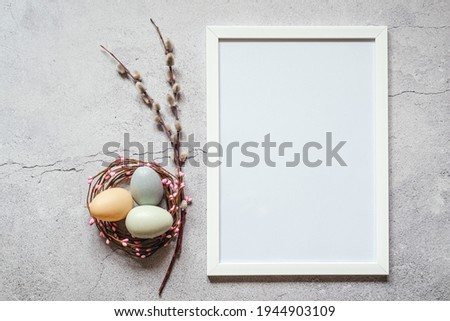 Easter minimal background with white picture frame, Easter eggs in bird's nest and pussy willow catkin branches.