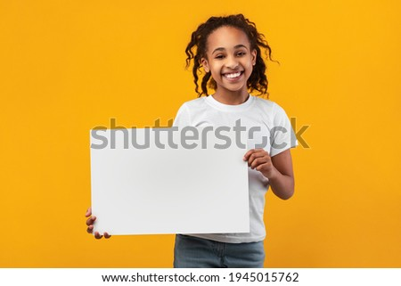 Cheerful Black Girl Holding And Showing Blank Paper Poster For Your Text Smiling To Camera Standing Isolated Over Yellow Studio Background. Kid With White Square Board For Advertising