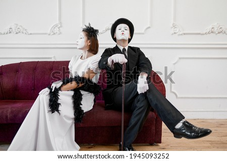 Mime artists, lady and gentleman sitting on sofa