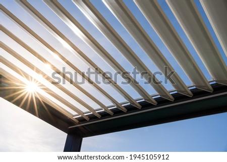Trendy outdoor patio pergola. the sun's rays pass through the metallic structure Royalty-Free Stock Photo #1945105912