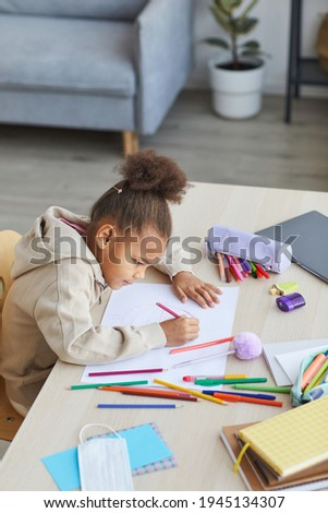 High angle portrait of cute African-American girl drawing pictures while sitting at desk in cozy home interior, copy space