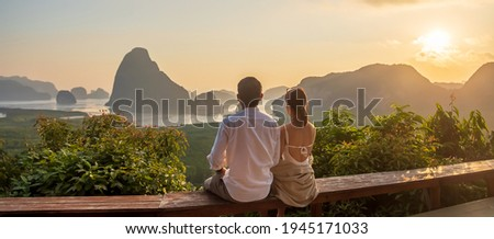 Happy couple traveler enjoy Phang Nga bay view point, Tourists relaxing at Samet Nang She, near Phuket in Southern Thailand. Southeast Asia travel, trip, love, together and summer vacation concept Royalty-Free Stock Photo #1945171033