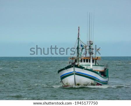 SMALL WOODEN FISHING BOAT AT SEA