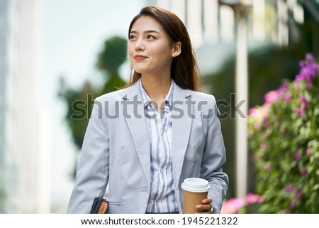successful young asian female white collar office worker walking on street looking away holding cup of coffee Royalty-Free Stock Photo #1945221322