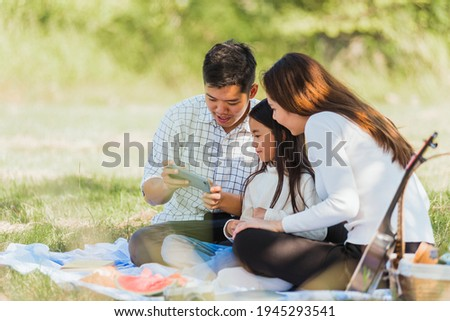 Happy Asian young family father, mother and child little girl having fun and enjoying outdoor sitting on picnic blanket looging picture after taking selfie by mobile smart phone at summer garden park