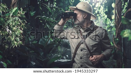 Brave explorer walking alone in the jungle he is looking through binoculars Royalty-Free Stock Photo #1945333297