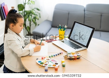 Serious little girl handwrite study online using laptop at home, cute happy small child take Internet web lesson or class