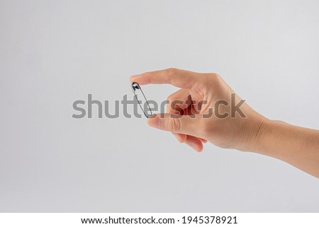 hand holding safety pins Isolated on white background Royalty-Free Stock Photo #1945378921