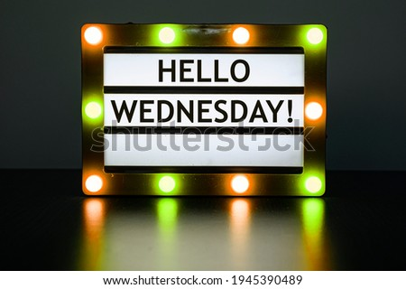 Lightbox with yellow and orange lights in dark room with words - Hello Wednesday! Royalty-Free Stock Photo #1945390489