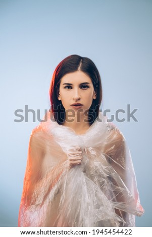 Beauty enhancement. Skincare treatment. Plastic surgery. Brunette pretty woman with smooth face neck body covered with wrinkled polyethylene film isolated on blue copy space background.