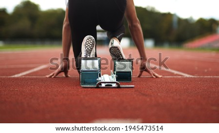 Track and Field Athlete being ready in the blocks alone with no competition, sprinter, empty lanes, lonely, training, practise, spikes Royalty-Free Stock Photo #1945473514