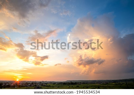 Dramatic sunset landscape of rural area with stormy puffy clouds lit by orange setting sun and blue sky. Royalty-Free Stock Photo #1945534534