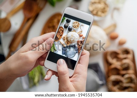 Food blogger taking a picture with her phone of groceries on white table. Picture of ingredients for breakfast on smartphone. Blogging concept.