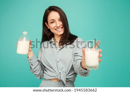 Photo of attractive lady smiles and drinks milk, dairy products. Wears grey shirt, isolated turquoise color background.