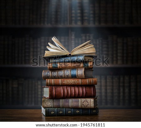A stack of old books on table against background of bookshelf in library. Ancient books as a symbol of knowledge, history, memory and information. Conceptual background on education, literature topics Royalty-Free Stock Photo #1945761811